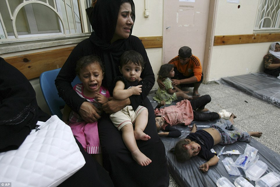 Innocent victims: A mother cradles her two children, while other toddlers lies on a mat next to her, at a hospital in Rafah