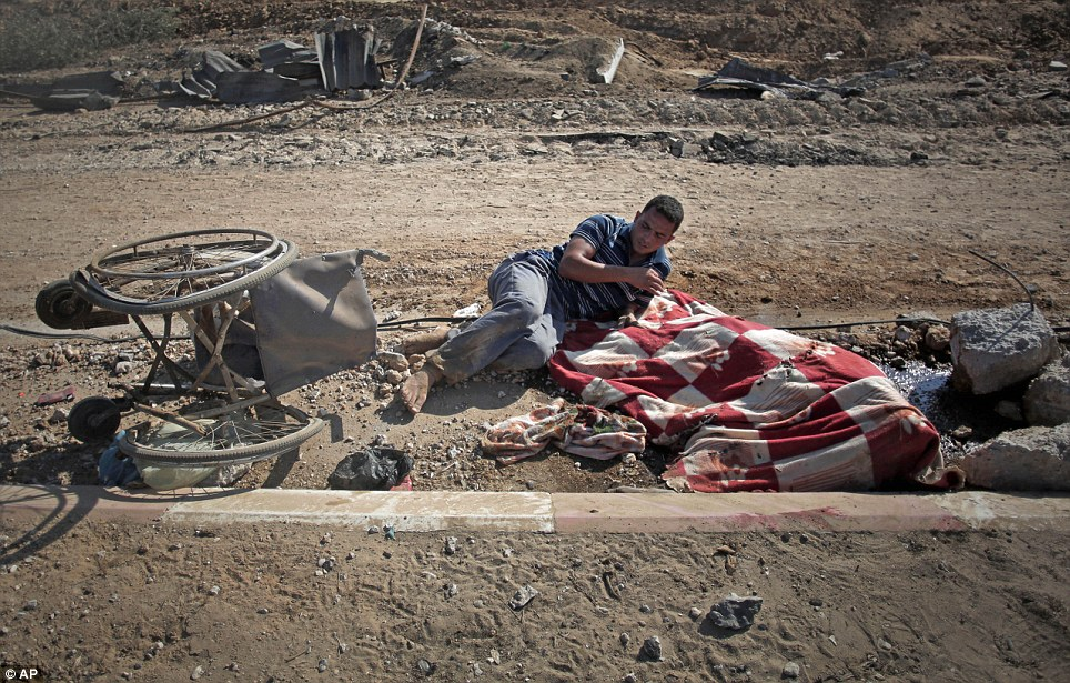 Appalling loss of life: Palestinian Nidal Abu Rjeilah, 30, leans over the blanket-covered corpse of his disabled sister Ghadeer, 17, in the southern Gaza village of Khuzaa