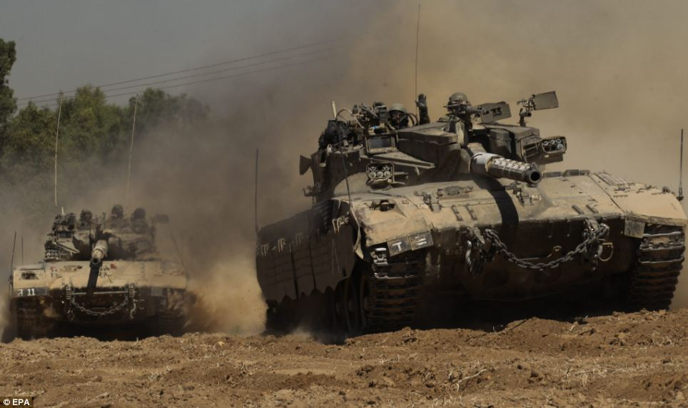 On the move: Israeli Merkava tanks are pictured travelling in southern Israel towards the border with Gaza after the ceasefire collapsed this morning