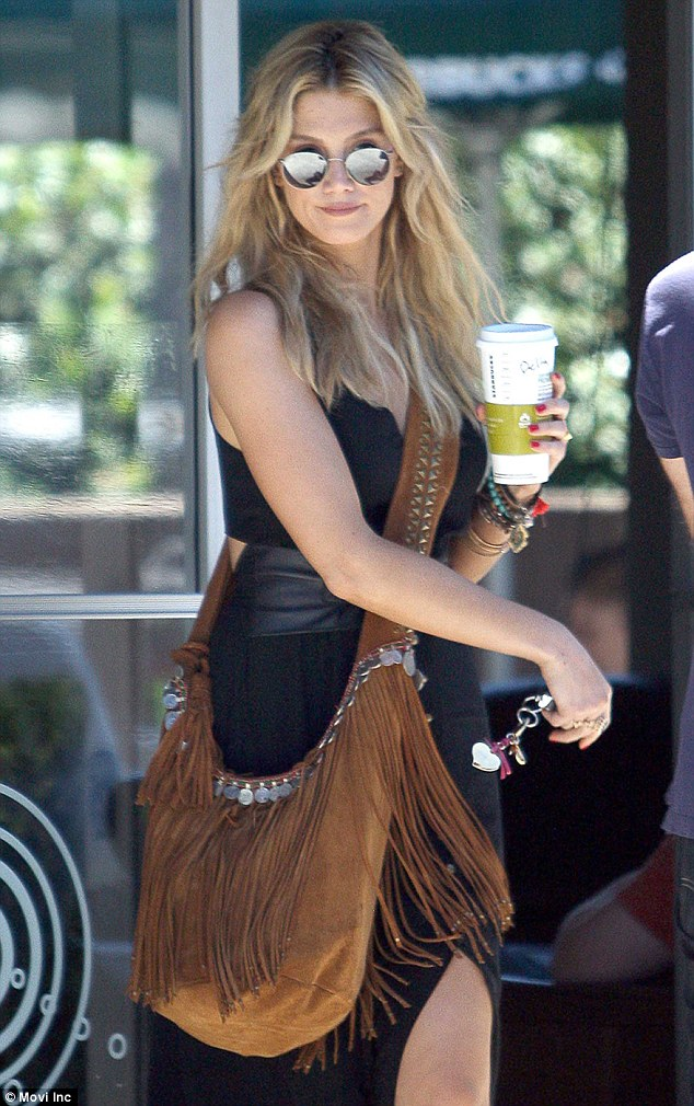 Peace out: Channeling her inner Janis Joplin, the 29-year-old Innocent Eyes singer accessorised her black cotton dress with a leather belt wrapped around the very top of her waist and a caramel, suede shoulder bag with tassel and silver trinket detailing
