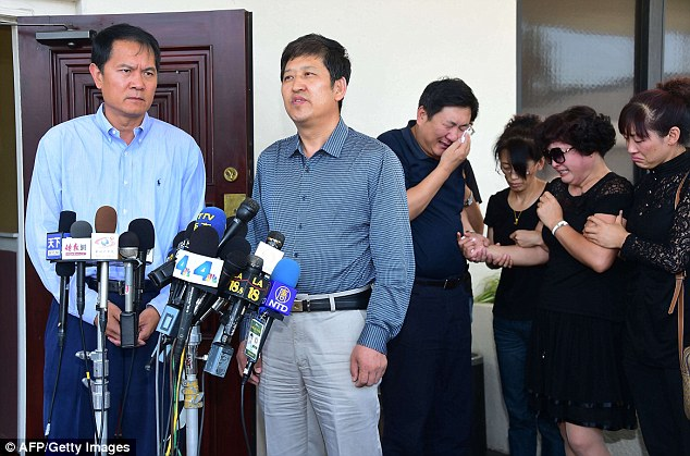 Help at hand: The father, Ji Songbo  and mother Du Jinhui  could not hold back their tears while assited by family members as a cousin of the father, Liu Lisheng (L) and English translator George He (R) made statements to the media