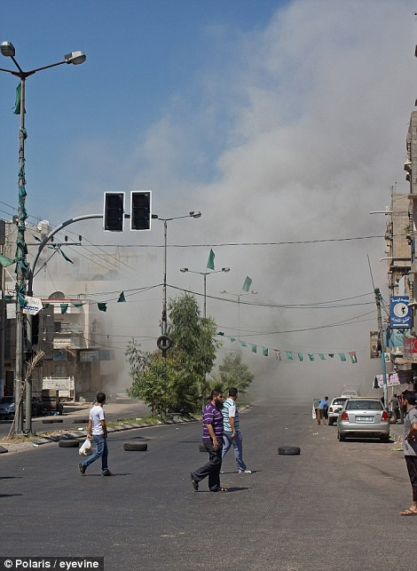 Residents of central Gaza City watch as an Israeli air strike destroys an apartment building