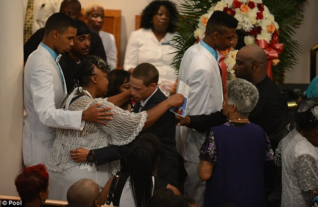 Community gathers: Gwen Carr (left) hugging Ramsey Orta, the civilian who video recorded the incident with NYPD and the late Eric Garner (Carr's son)