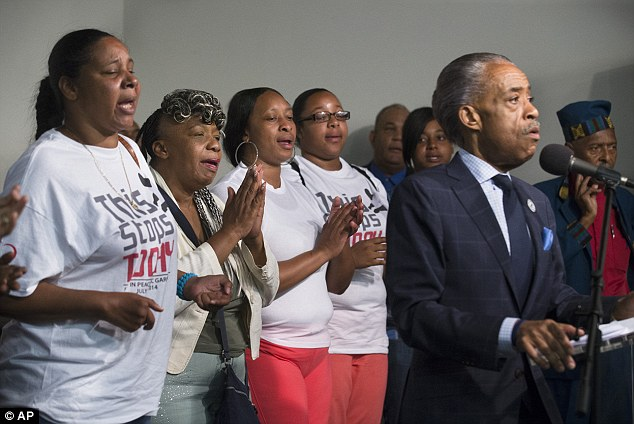 Civil rights investigation: (left to right) Wife of Eric Garner, Esaw Garner, his mother Gwen Carr, his sister Ellisha Garner, and his daughter Emerald Garner, sing behind the Reverend Al Sharpton as he speaks during a rally at the National Action Network headquarters, Saturday, July 26