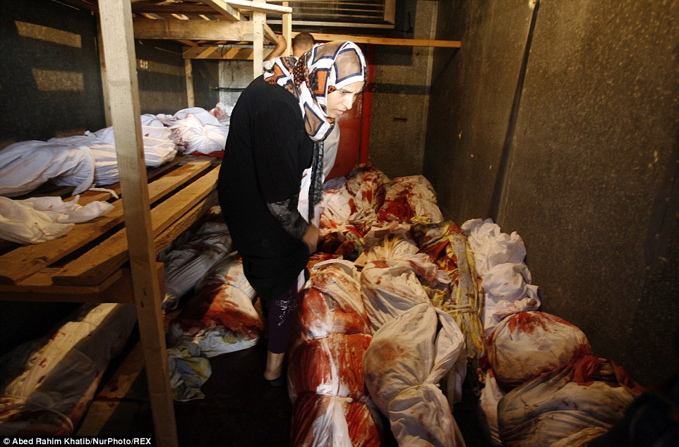 Horror: A Palestinian relative stands in the fridge among the mass of bodies, which have been bound up in blood-stained white sheets after Israeli strikes