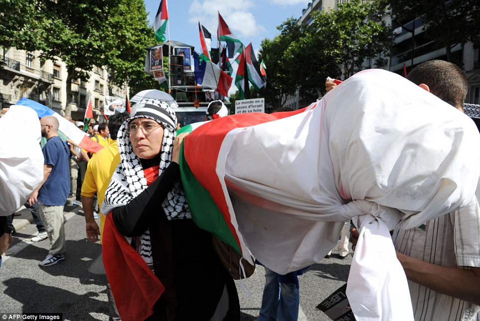Bodies: Another protester stands in solidarity with Palestine in Paris, holding up a fake body draped in the Palestinian national flag