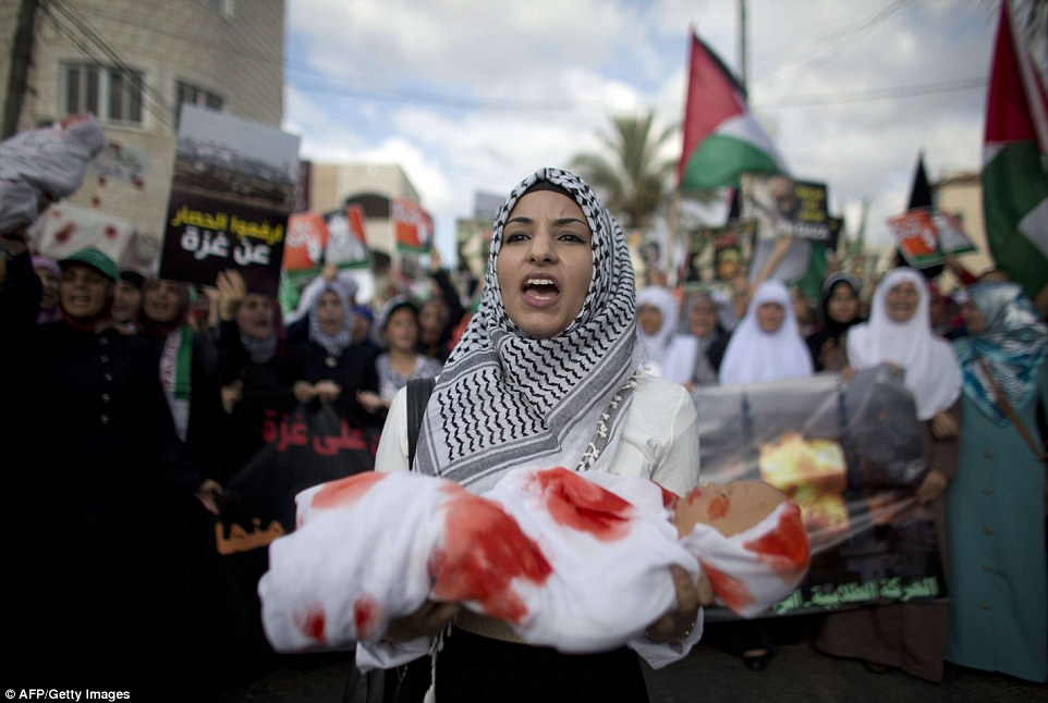 Anger: An Arab-Israeli woman holds a mock bloodied corpse at the Tamra protest yesterday, flanked by Palestinian flags