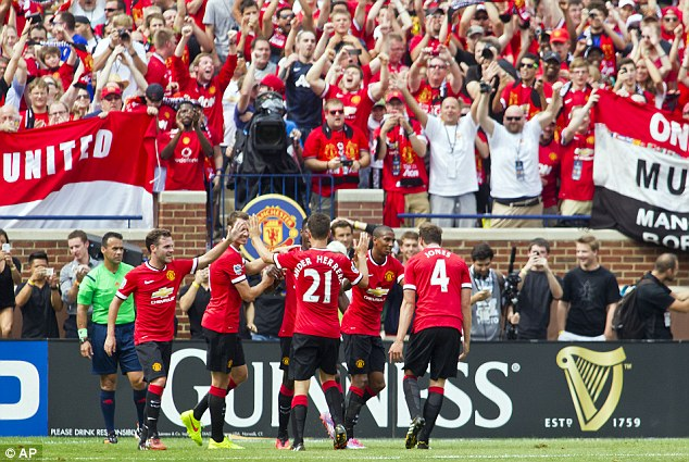 Celebrate: Young's team-mates rush over to congratulate him after he put United ahead in the first half