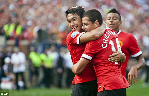 All smiles: Shinji Kagawa hugs Javier Hernandez after he scored United's third and final goal with his head