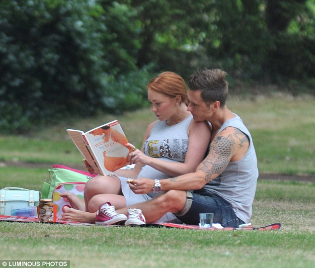 Doing their homework: The pair cuddled up as they read pregnancy book together on their tartan rug