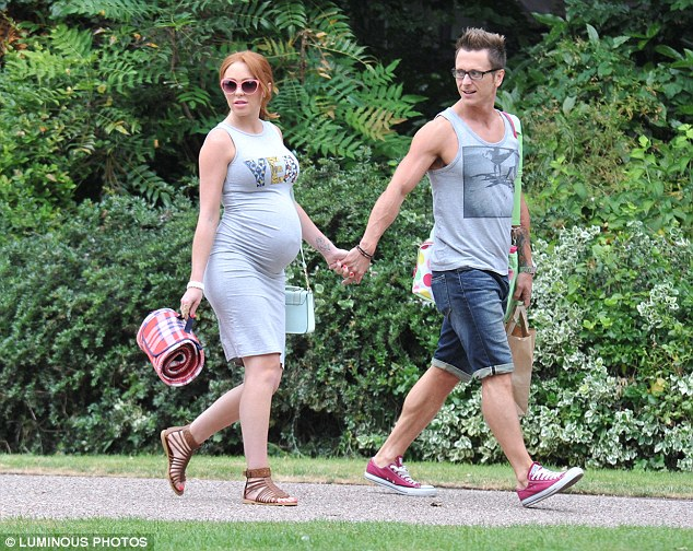 Hand-in-hand: The 32-year-old's burgeoning belly was impossible to miss in her grey T-Shirt dress, complete with 'Yeah' motif