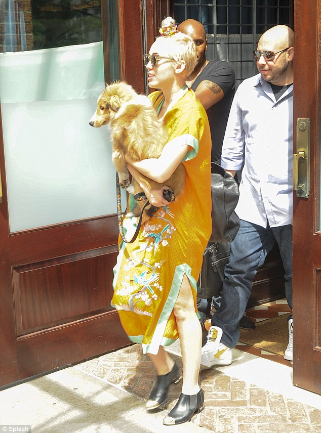 Buddies: The Wrecking Ball singer made sure to keep her new Rough Collie, Emu, close as she walked out of the hotel with him in her arms