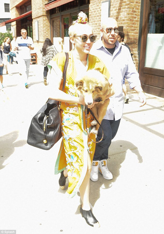 Quite the look: Miley Cyrus was decked out in a long gold satin kimono-inspired dress as she exited her New York hotel holding her adorable dog Emu on Saturday