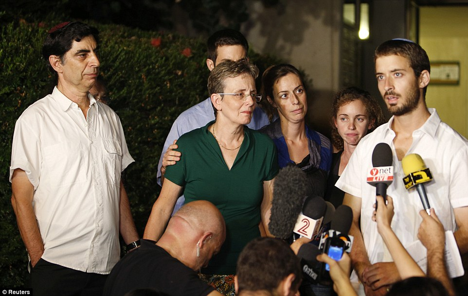 Tension: In the early hours today the Israeli Defence Force (IDF) revealed Lieutenant Hadar Goldin, 23 - whose supposed kidnap by Hamas caused a ceasefire to break down - in fact died in the line of duty. Pictured are Members of Lieutenant Goldin's family, including his brother Zur, right, outside their home in Kfar Saba