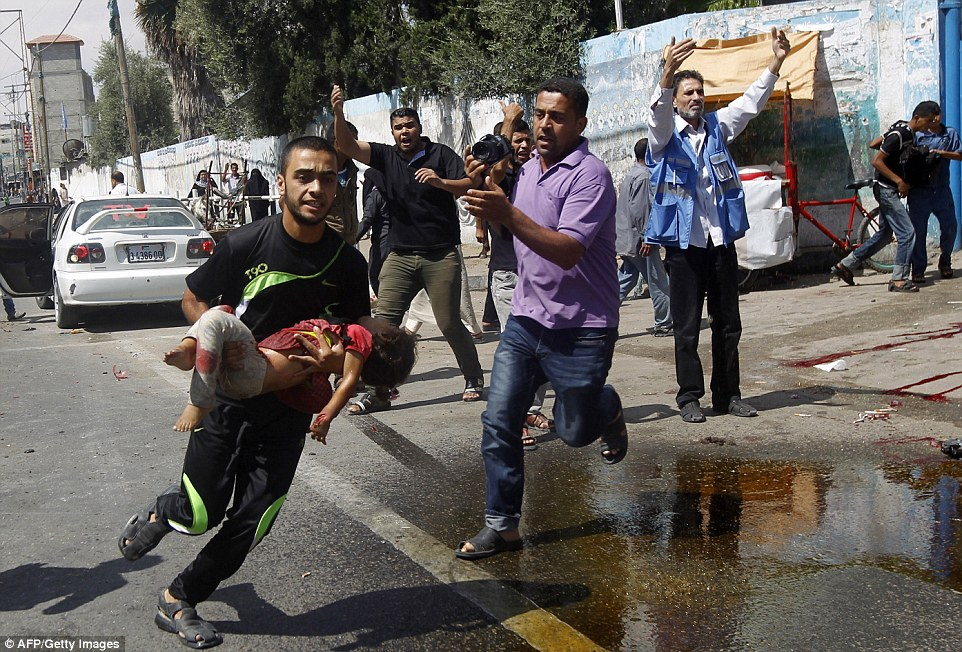 Hurt: A Palestinian man runs in the street with an injured child after the reported Israeli military strike on a UN school in Rafah, in the southern Gaza Strip