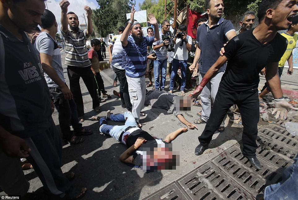 Anguish: Palestinians react as wounded and dead people lie on the ground following what witnesses said was an Israeli air strike at a UN-run school in Rafah