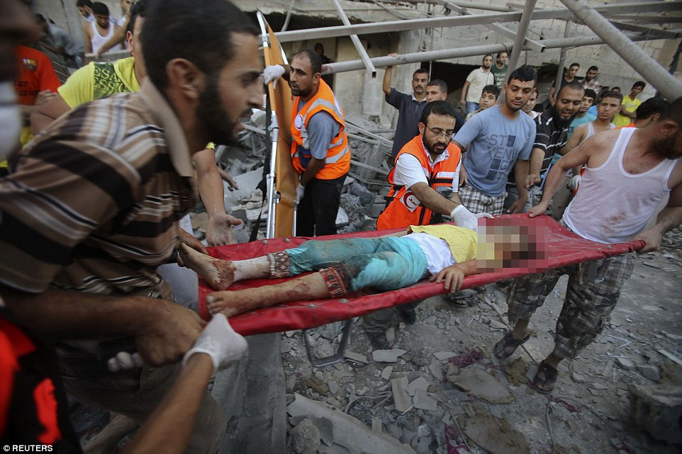 Death: Palestinians carry the body of a girl who was found this morning under the rubble of a house where at least nine members of the al-Ghol family died in Rafah