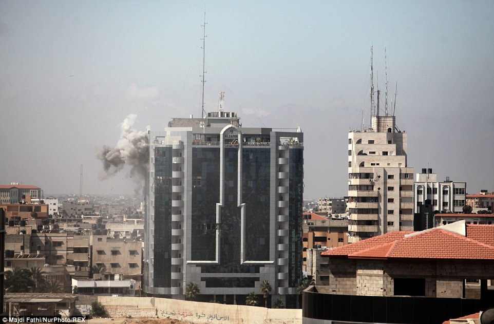 Strikes: Smoke rises from the Al Zafer tower apartment in Gaza City, which was damaged by an Israeli strike this morning as the conflict entered its 27th day