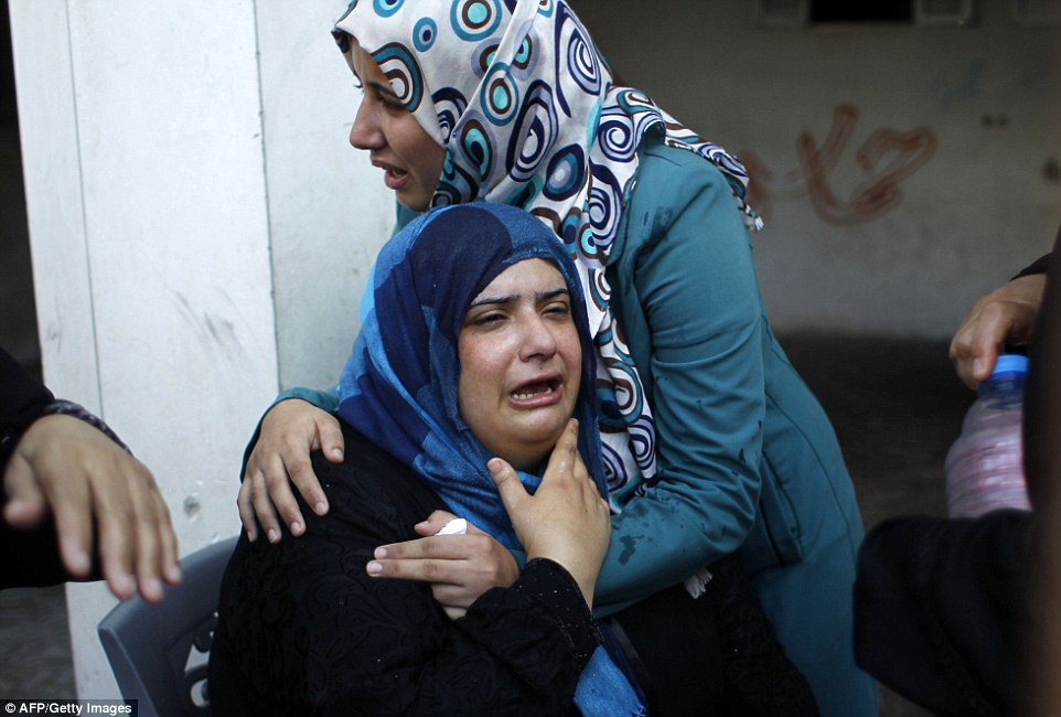 Mourning: Relatives of the family which lost at least nine of its members in a strike on a house in Rafah earlier today. Dozens were killed in the fresh wave of violence
