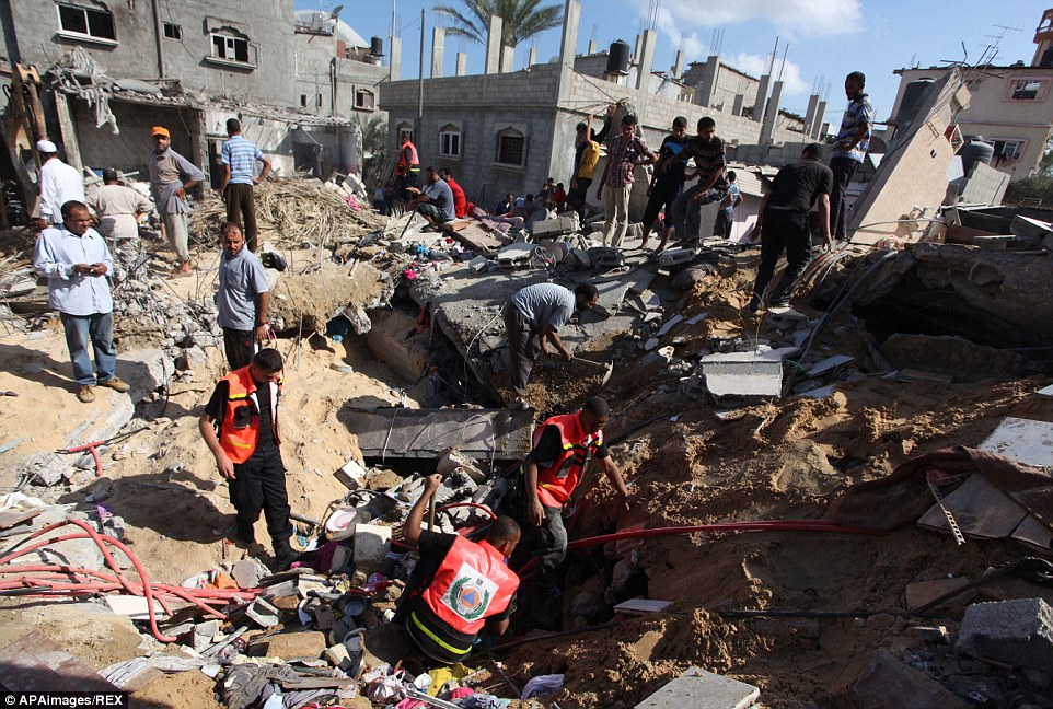 Another family killed: Rescue workers search for victims where at least five members from the al-Khattab family died in Deir al-Balah in the central Gaza Strip today