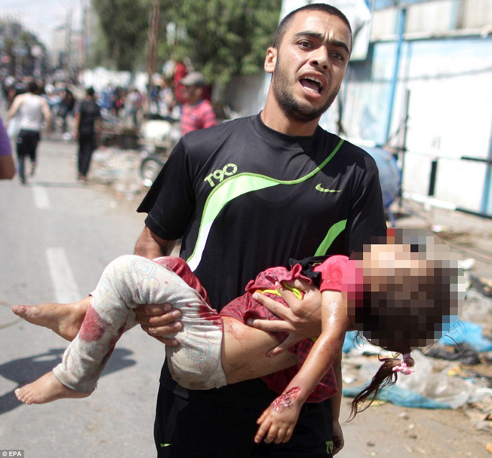 Deaths: A man carries a dead girl from the UN school in Rafah, which was hit by an airstrike today as the number of people in 90 UN-run shelters neared 270,000