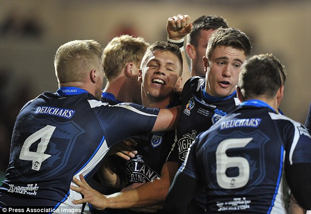 Joy: Matthew Russell is congratulated by his team-mates after scoring a try for Scotland