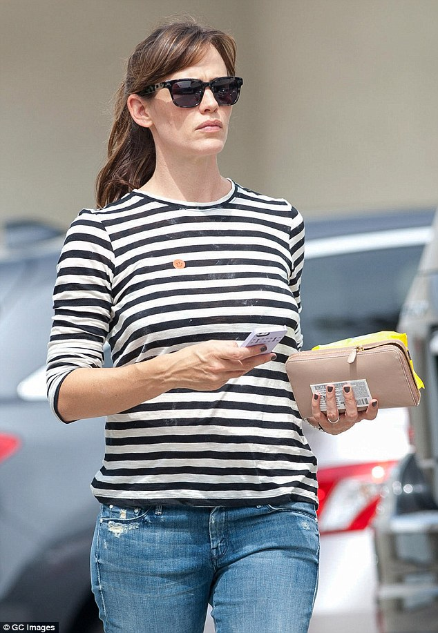 Hiding something? The 42-year-old was wearing a loose-fitting striped shirt, perhaps trying to hide her growing bump