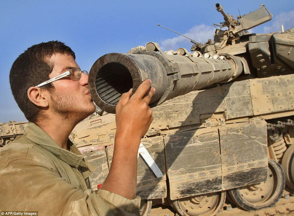 An Israeli soldier kisses his Merkava tank along the border between Israel and the Gaza Strip after he, along with many other soldiers, pulled out of ground assaults