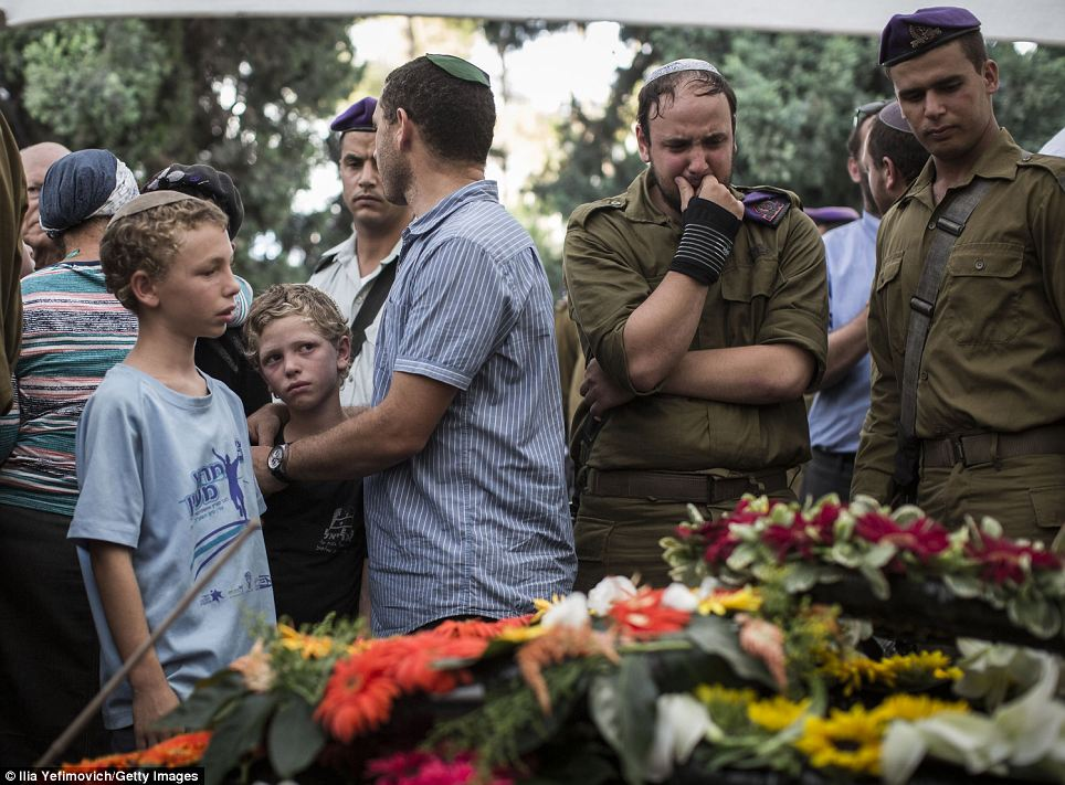 Mourning: Friends and relatives of Lt Goldin crowd around his flower-bedecked coffin during his funeral yesterday