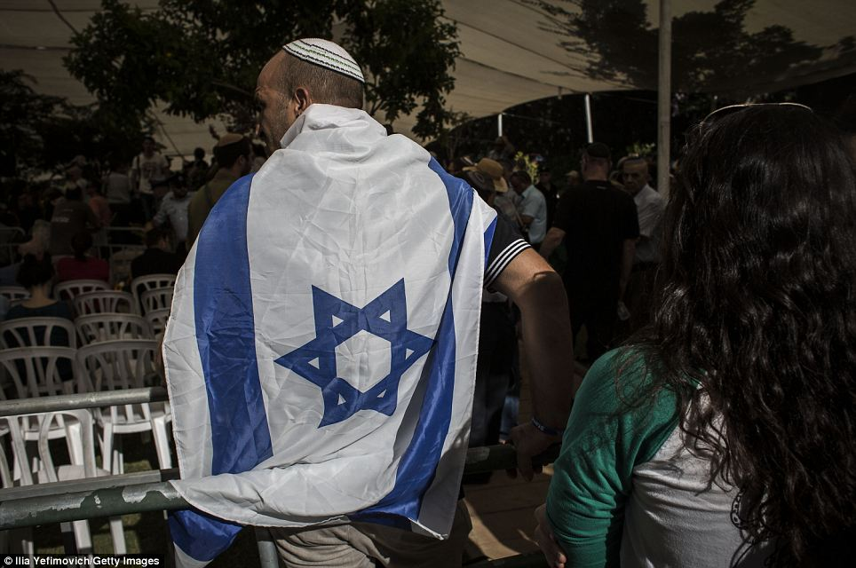 A man stands draped in an Israeli flag: A military panel reached the conclusion that he must have died based on evidence at the scene of the attack, the IDF said
