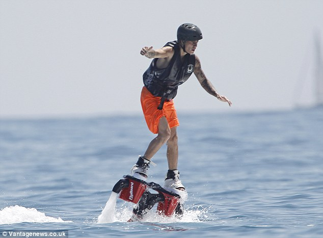 The beach boy! The Canadian native wore oversized orange boardshorts as he took to the sea