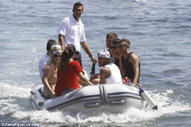 Chilling out: Neymar is joined by a group of pals on a boat