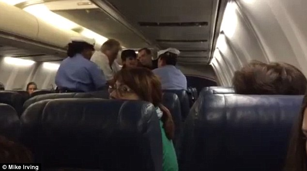 Marching orders: The female passenger was eventually put in handcuffs and removed from the jet while shocked passengers watched on