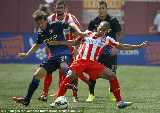 Pairs: David Silva and Mathieu Dossevi battle for the ball while flanked by Giannis Maniatis ad Stevan Jovetic