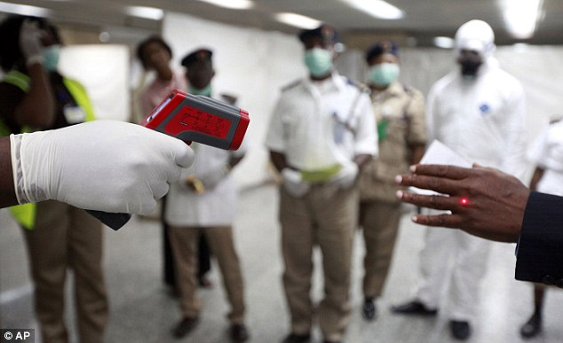 High alert: A Nigerian health official uses a thermometer at Murtala Muhammed Airport to screen for Ebola
