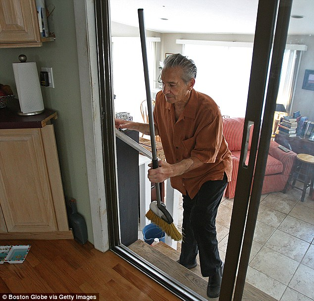 Back to it: Mangino is seen here doing chores one year after his transplant