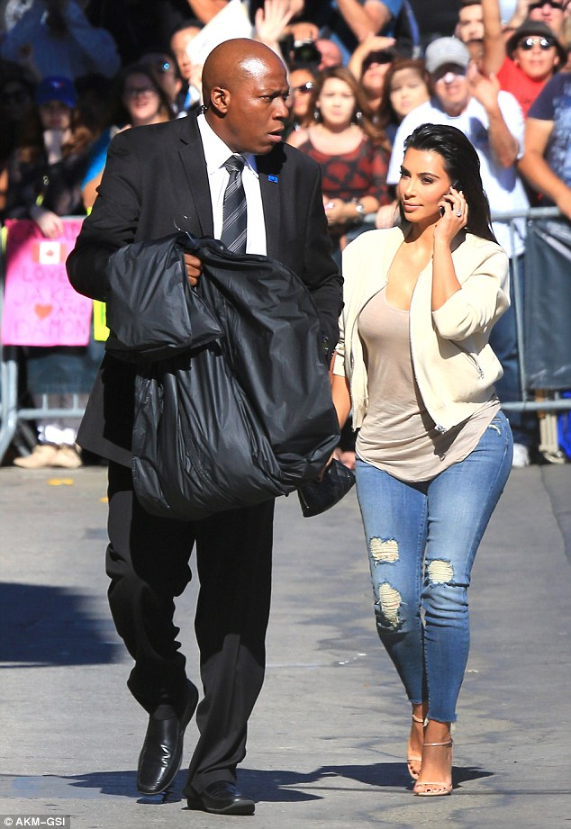 Doing the heavylifting: Kim had a bodyguard carry her garment bag, which presumably contained her outfit her appearance on the late night talk show