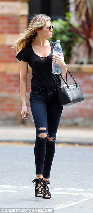 Power walk: The 28-year-old model added length to her lean pins with a pair of black peep toe heels while she kept her face hidden behind a pair of black circular shades