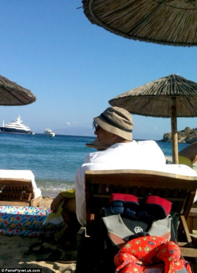 A place in the sun: Mr Mittal looks out to sea at the huge yacht anchored in front of him