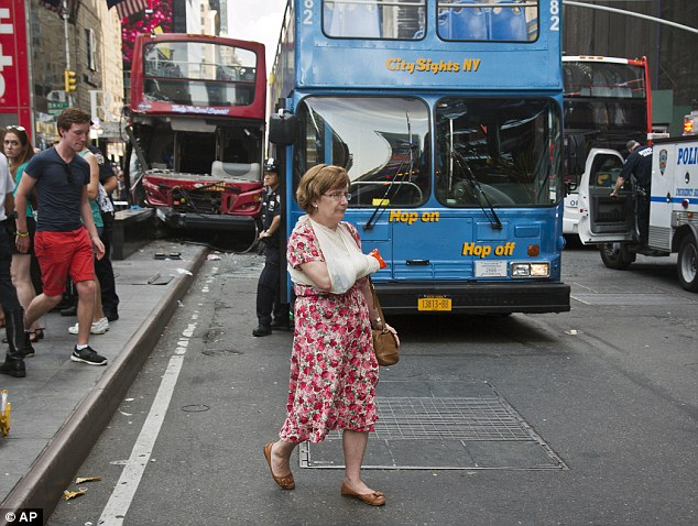 Injured: A woman leaves after being treated at the scene of a traffic accident involving two double-decker tour buses in New York City's Theater District on Tuesday August 5, 2014