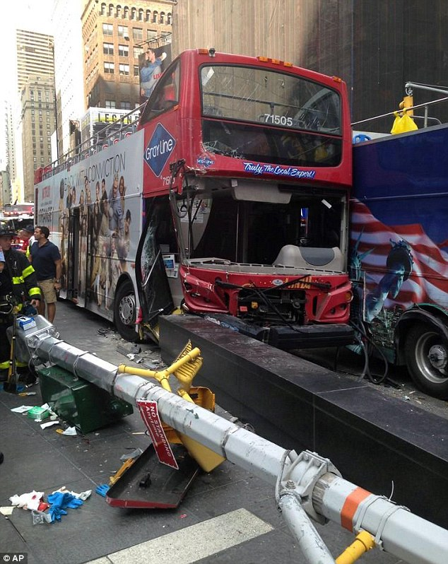 Wreck: The driver of this Gray Line tour bus has been arrest following a collision between double-deckers in New York City's busy Time Square on Tuesday afternoon