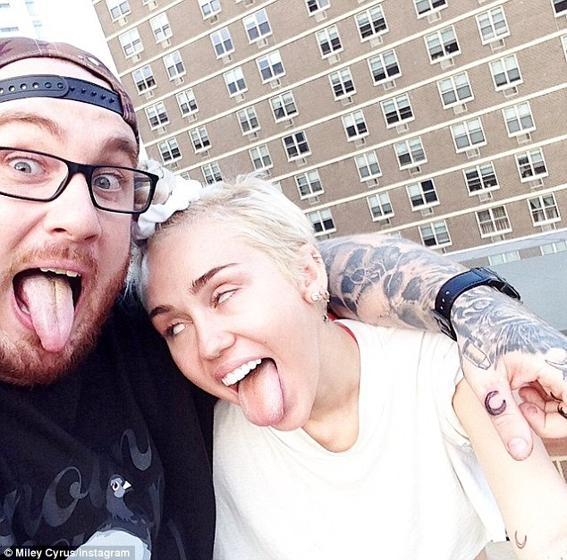 Bonding: The pair showed off their matching crescent moon tattoos and Miley persuaded Bang Bang to pull her signature pose