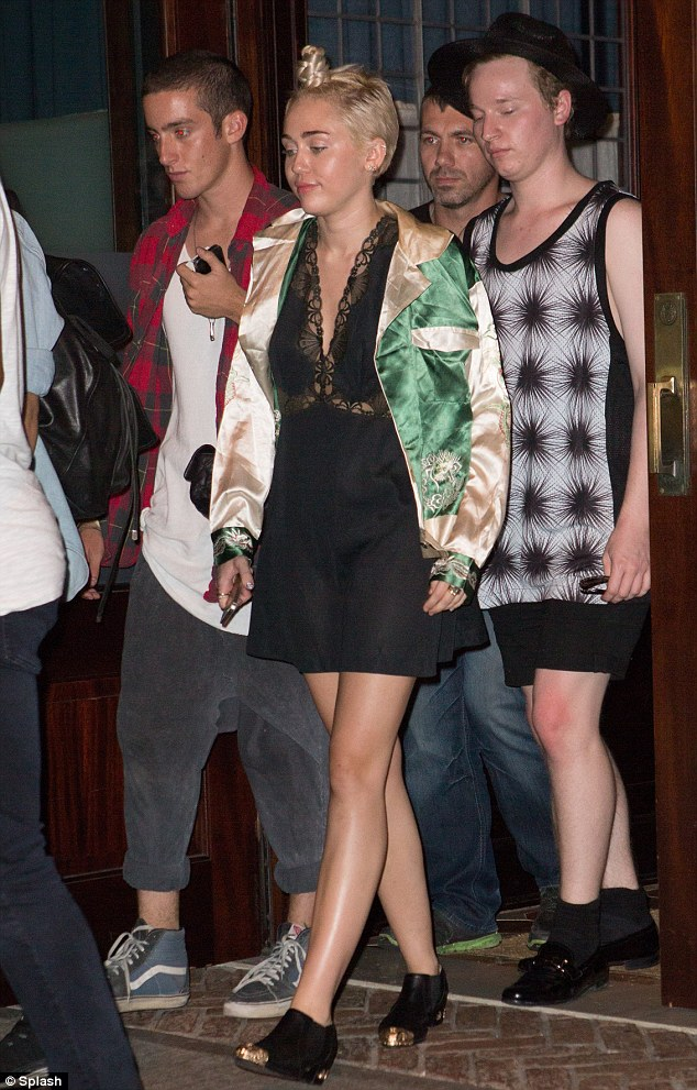 We can't stop: Party-loving Miley heads out into the night with a gaggle of male friends.