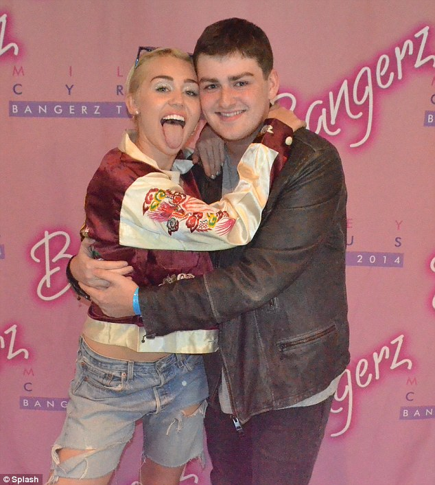 Fun times: Miley met with a fan backstage on Friday at the New York Nassau Colisseum