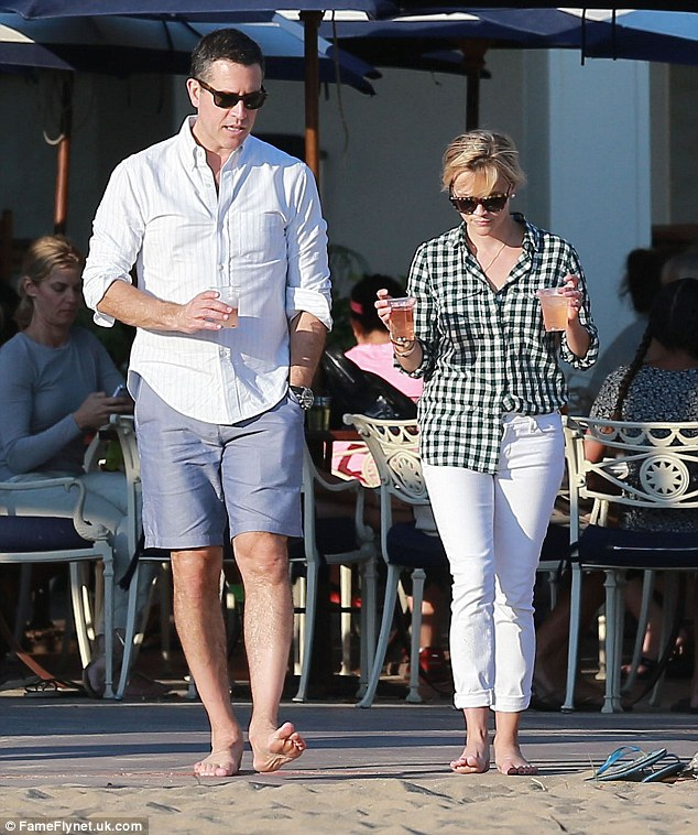Toe-ing the line: Reese Witherspoon and her husband Jim Toth go barefoot on the beach as they enjoy drinks in Santa Monica, Califronia, on Wednesday