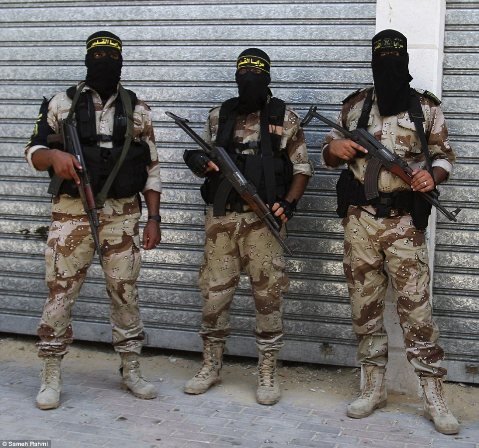 Militant: Palestinian fighters from Islamic Jihad hold their weapons at the funeral of a fellow militant in Gaza