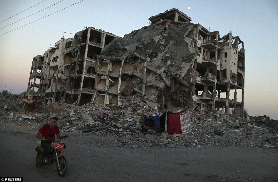 Aftermath: A Palestinian rides past residential buildings in Beit Lahiya town, all but obliterated by Israeli shelling and air strikes, in the northern Gaza Strip