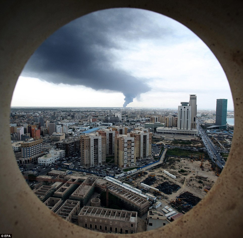 A city at war with itself: Smoke fills the sky over Tripoli following a rocket attack which struck and ignited a tank in the city's main fuel depot on Sunday