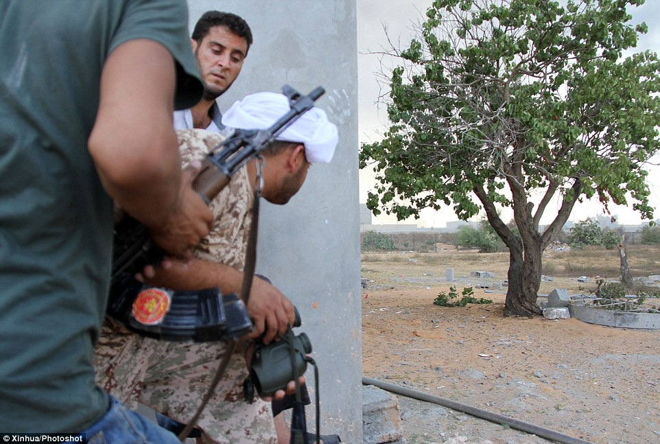 Battle: Militiamen take cover as they fight for control of the airport