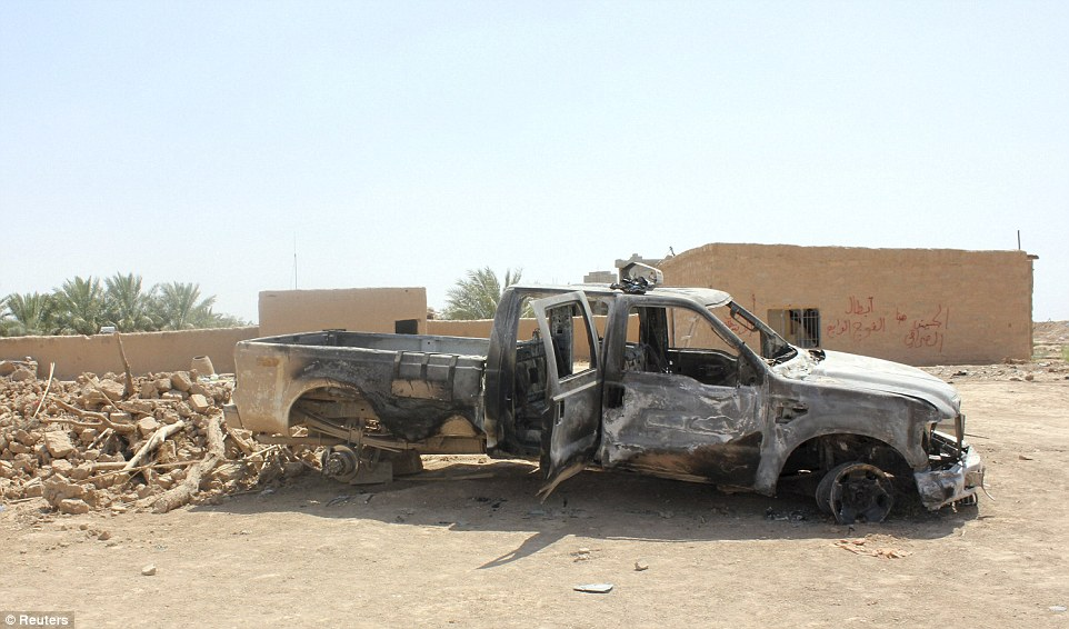 Wreckage: A burnt vehicle of the Iraqi security forces is seen in Udhaim district, north of Baghdad, where they repelled repeated attacks from Islamic State militants